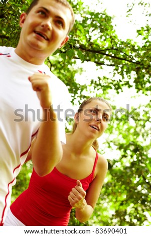 Image of happy young female running with boyfriend near by - stock photo