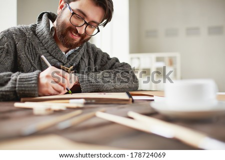 Image of happy young man drawing - stock photo