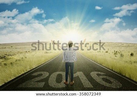 Image of happy young man standing on the road with numbers 2016 and bright sun light - stock photo