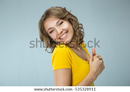 Image of happy young woman wearing yellow shirt and jeans shorts  over grey background