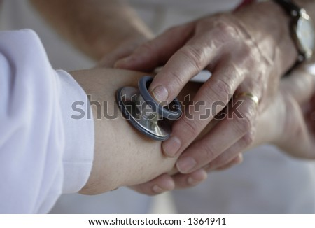 Image of healthcare professional taking blood pressure - stock photo