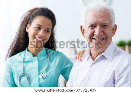 Image of helpful afroamerican caregiver and old man - stock photo