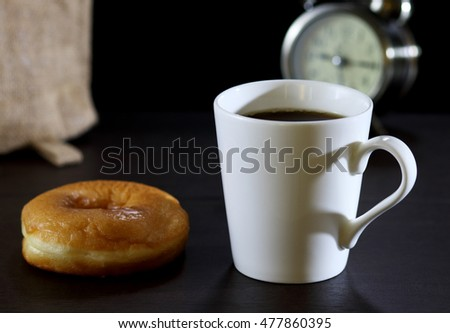 image of hot black coffee in white cup with donut on table