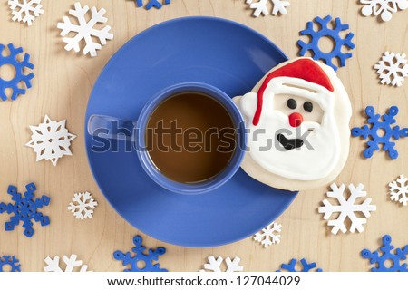 Image of hot chocolate and santa face cookie on blue plate with snow flakes - stock photo