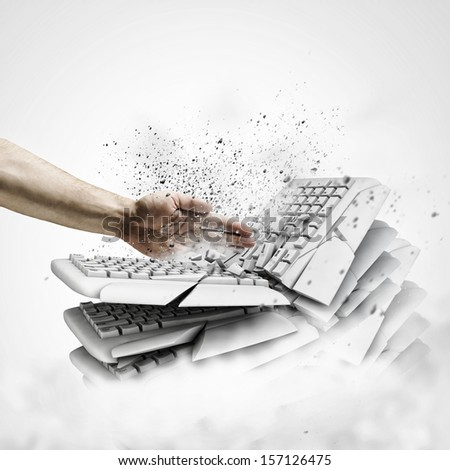 Image of human hand breaking pile of keyboards - stock photo