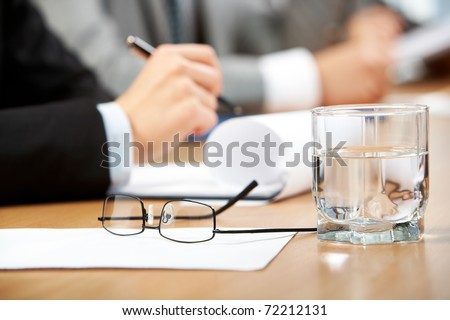 Image of human hand holding pen with glass of water, eyeglasses and paper near by - stock photo