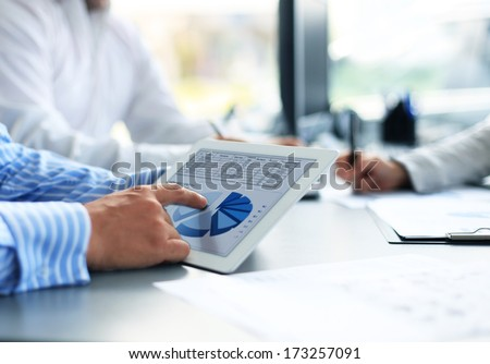 Image of human hand pointing at touchscreen in working environment at meeting  - stock photo