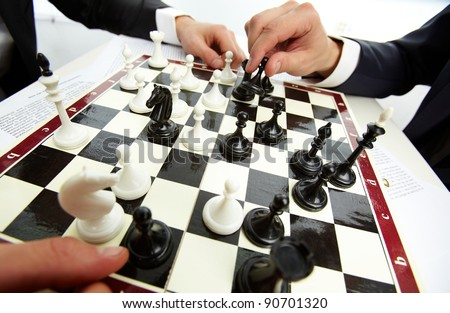 Image of human hand with chess figure making move - stock photo