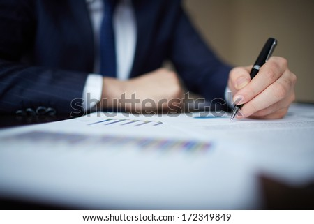 Image of human hand with pen over documents at workplace - stock photo