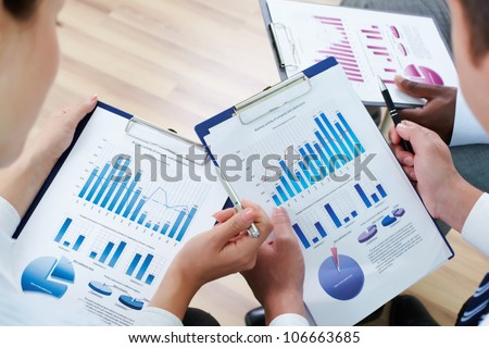 Image of human hands during discussion of business documents at meeting - stock photo