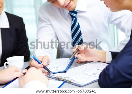 Image of human hands during discussion of business plan at meeting - stock photo