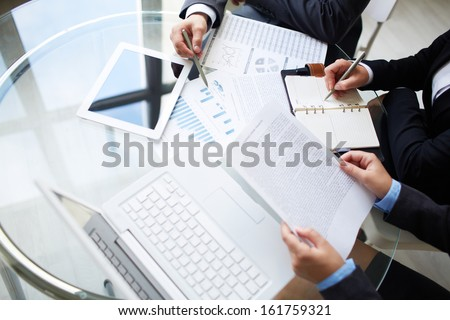 Image of human hands during paperwork at meeting  - stock photo