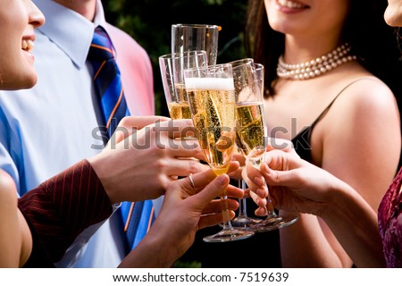 Image of human hands holding the glasses of champagne making a toast