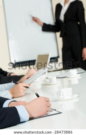 Image of human hands making notes on paper at seminar or conference