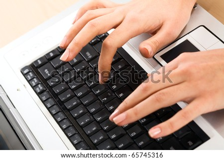 Image of human hands pressing keys of laptop