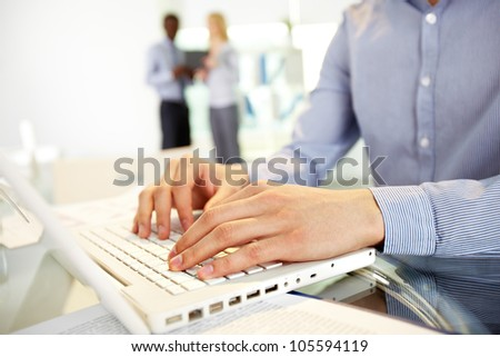 Image of human hands typing in the foreground, business colleagues can be recognized in the blurred background - stock photo