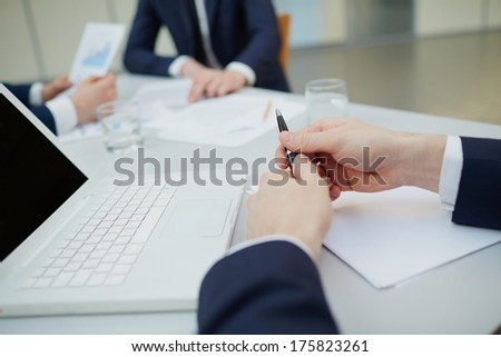 Image of human hands with pen during work planning at meeting