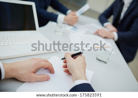 Image of human hands with pen writing business plan  - stock photo