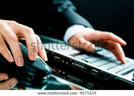 Image of human hands working on the laptop and computer mouse - stock photo