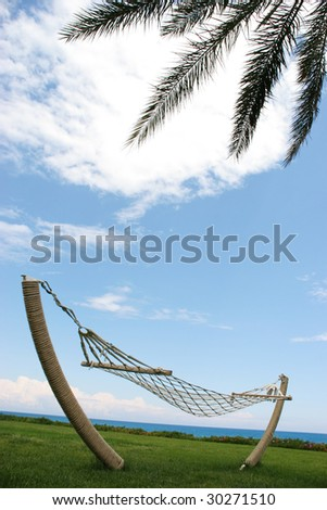 Image of idyllic place with empty hammock on grassland under palm branch and blue sky - stock photo