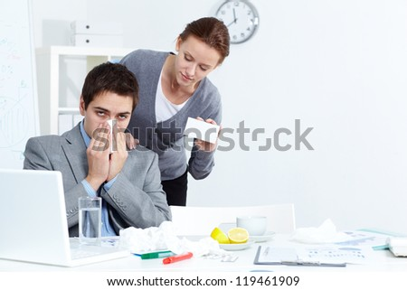 Image of ill businessman with handkerchief looking at camera while his partner offering him good medicine in office - stock photo