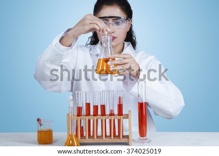 Image of indian female scientist working in the lab and doing research with chemical liquid - stock photo