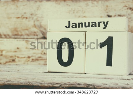 image of January First wooden vintage calendar on white background. retro filtered - stock photo