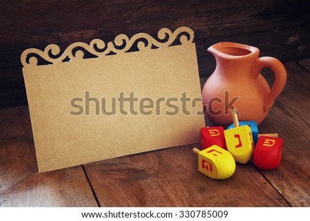 image of jewish holiday Hanukkah and wooden dreidels (spinning top) with empty card for adding text  - stock photo
