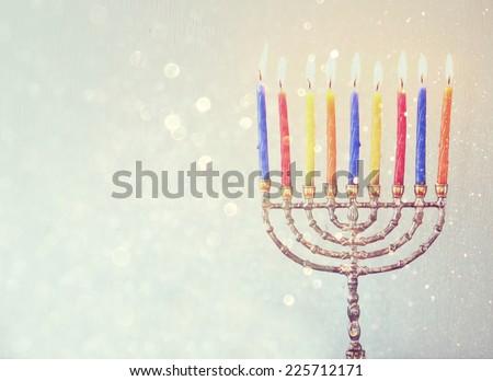 Image of jewish holiday Hanukkah background with menorah Burning candles over aqua glitter overlay - stock photo