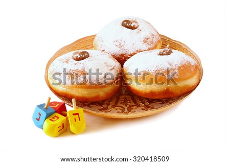 image of jewish holiday Hanukkah with donuts and wooden dreidels (spinning top). isolated on white  - stock photo