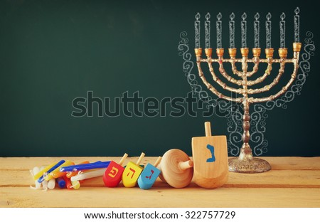 image of jewish holiday Hanukkah with drawing menorah candles (traditional Candelabra), wooden dreidels (spinning top) over chalkboard background  - stock photo