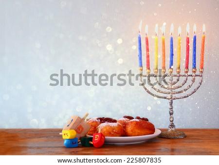 Image of jewish holiday Hanukkah with menorah, doughnuts and wooden dreidels (spinning top) - stock photo