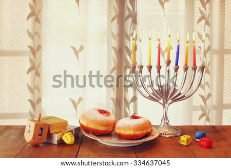 image of jewish holiday Hanukkah with menorah (traditional Candelabra) and wooden dreidels (spinning top) on table in front of the window - stock photo