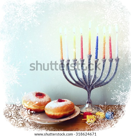 image of jewish holiday Hanukkah with menorah (traditional Candelabra), donuts and wooden dreidels (spinning top). retro filtered image with snowflakes and glitter overlay  - stock photo
