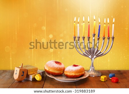 image of jewish holiday Hanukkah with menorah (traditional Candelabra), donuts and wooden dreidels (spinning top). glitter background  - stock photo