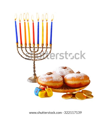 image of jewish holiday Hanukkah with menorah (traditional Candelabra), donuts and wooden dreidels (spinning top).isolated on white  - stock photo