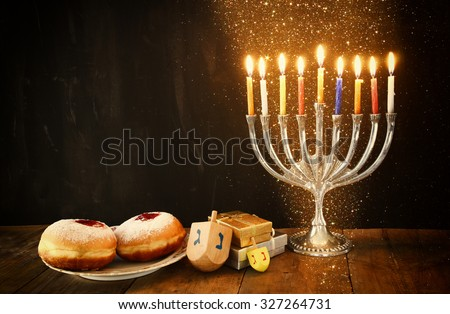image of jewish holiday Hanukkah with menorah (traditional Candelabra), donuts and wooden dreidels (spinning top). glitter night background  - stock photo