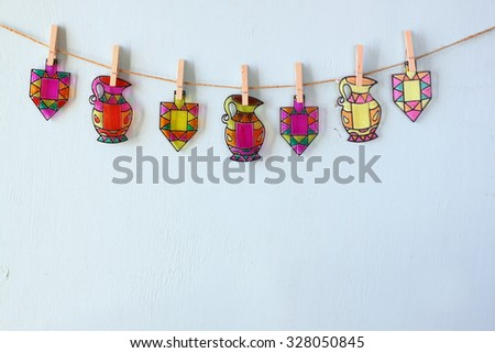image of jewish holiday Hanukkah with Stained-glass colorful dreidels (spinning top) hanging on a rope over wooden background  - stock photo