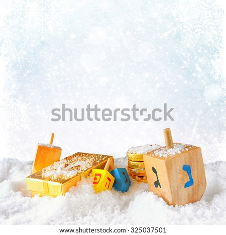image of jewish holiday Hanukkah with wooden colorful dreidels (spinning top) over december snow with glitter and snowflake background  - stock photo