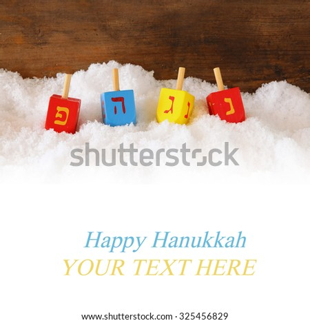 image of jewish holiday Hanukkah with wooden colorful dreidels (spinning top)  over december snow. copy space