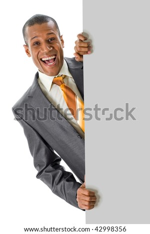 Image of joyful businessman peeping out of blank poster with your ad - stock photo