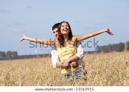 Image of joyful girl stretching arms while being embraced by her boyfriend - stock photo