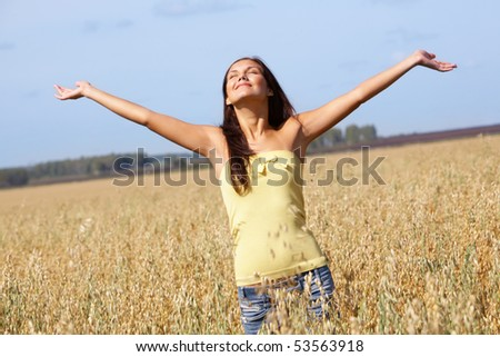 Image of joyful girl with stretched arms standing in the middle of rye field - stock photo