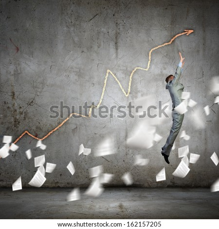 Image of jumping businessman trying to catch arrow of graph - stock photo