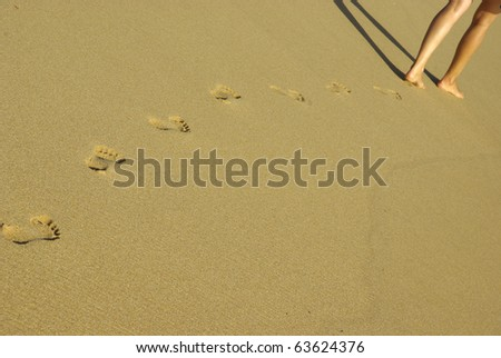 Image of lady footprints in the sand. - stock photo