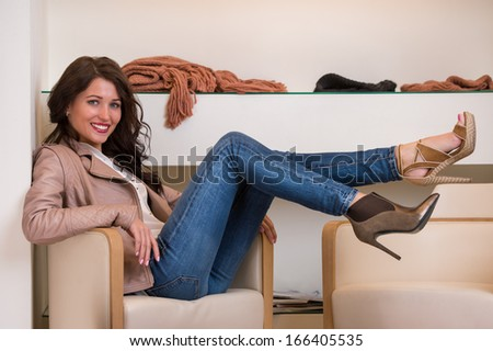Image of lady trying on several pairs of new shoes in the store - stock photo