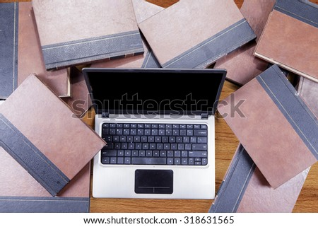 Image of laptop computer with empty screen and textbooks on the table - stock photo