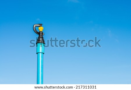 image of lawn sprinkler system with blue sky - stock photo