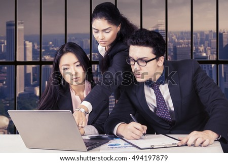Image of leader pointing on the laptop while her employees looking at the laptop and sitting in the office with city background on the window