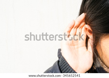 Image of listening, with a girl putting her hand on ear